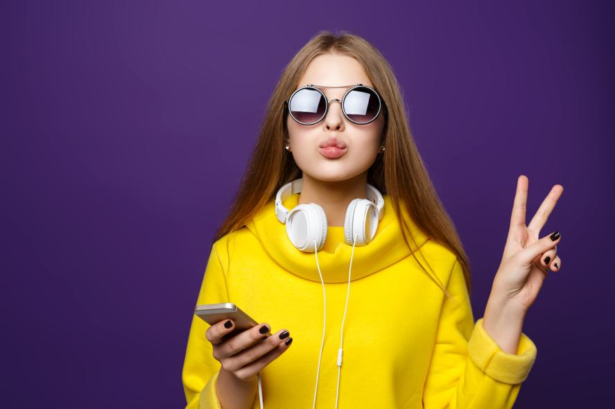 A teenager in sunglasses wearing headphones