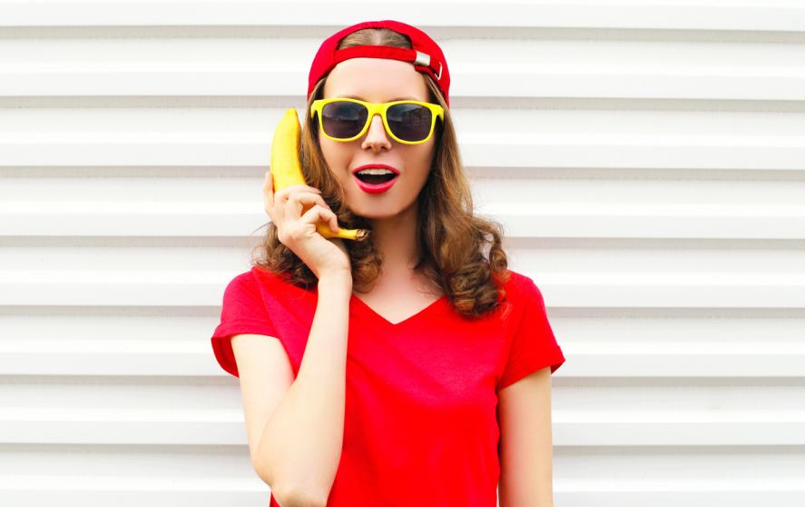 A woman in a red t-shirt using a banana as a phone