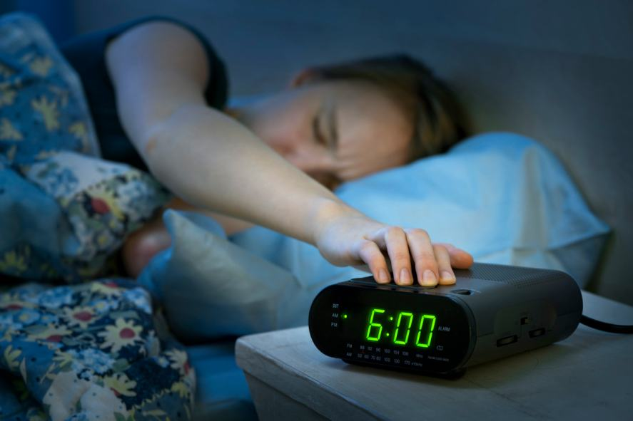 A person turning off their alarm clock