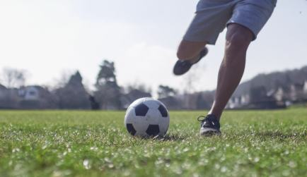 Man about to kick a football in the park