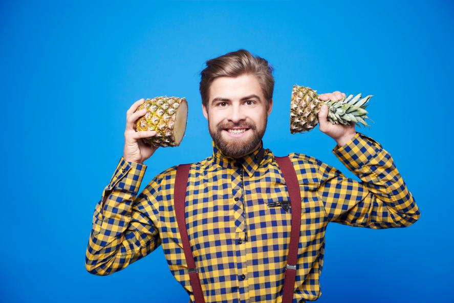 A man with two halves of a pineapple