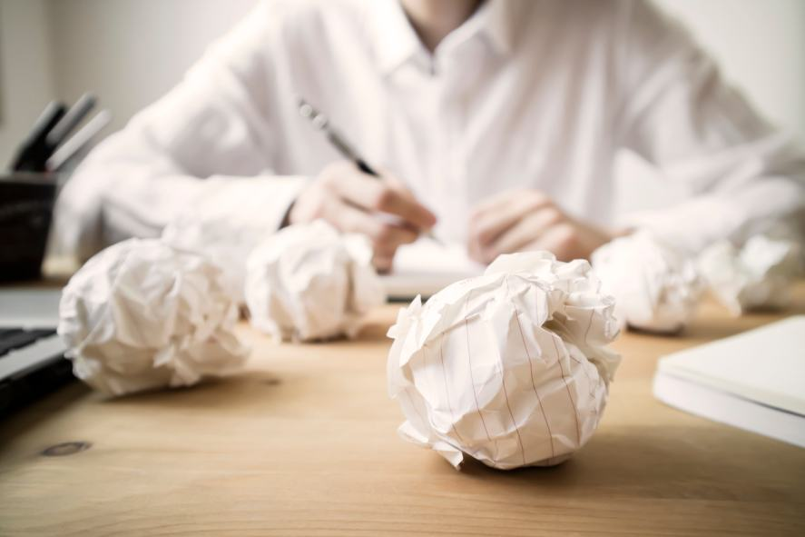 A writer surrounded by crumpled paper