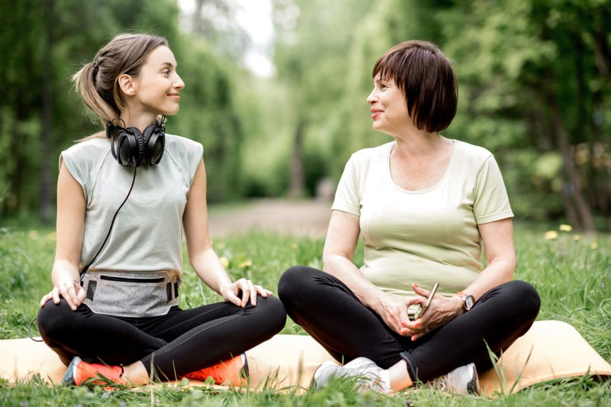 Two ladies doing yoga in a park