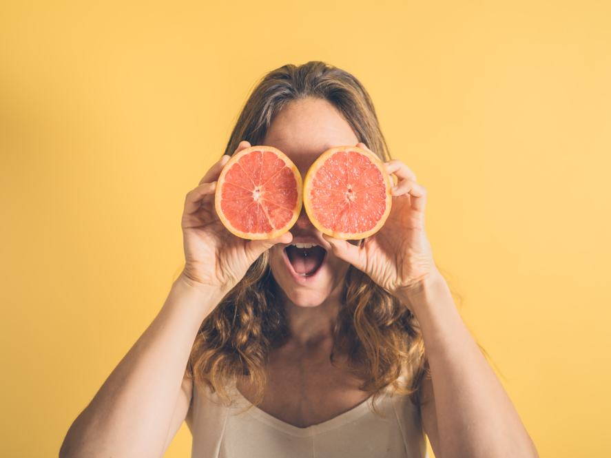 A woman using grapefruit as a pair of comedy eyes