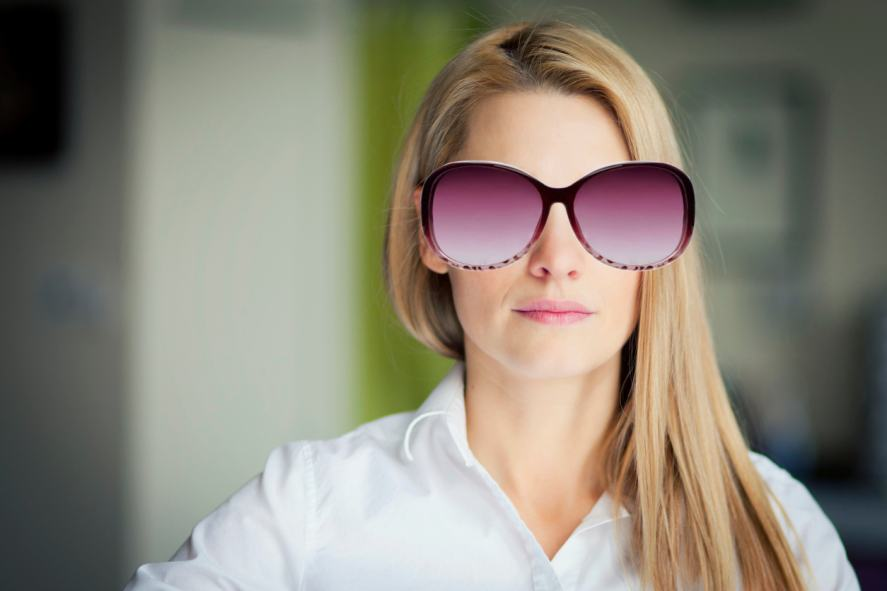 A woman wearing an oversized pair of purple sunglasses