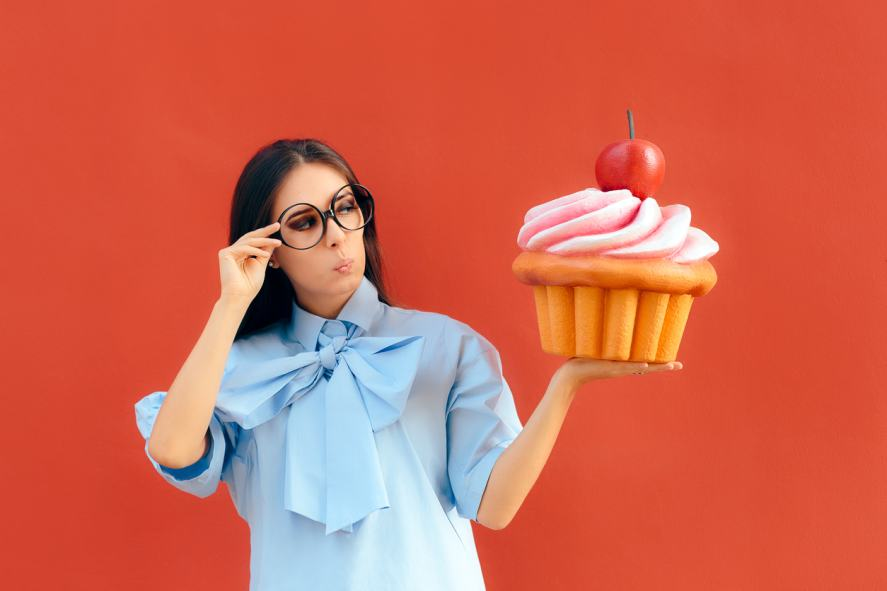 A woman holding a giant cupcake