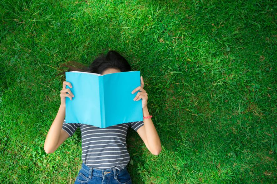 Someone lying on the grass and reading a big book