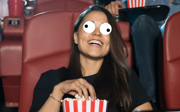 A woman watching a film and eating popcorn at the cinema