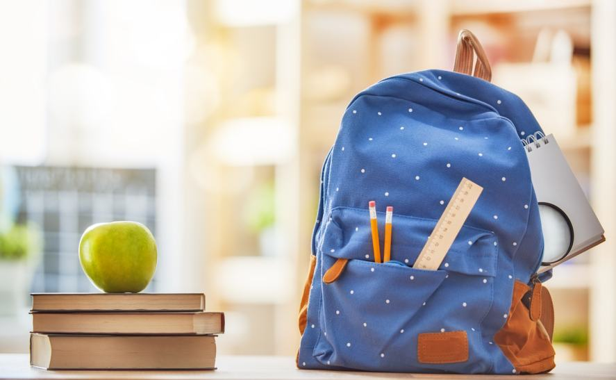 A school bag and an apple on top of some books