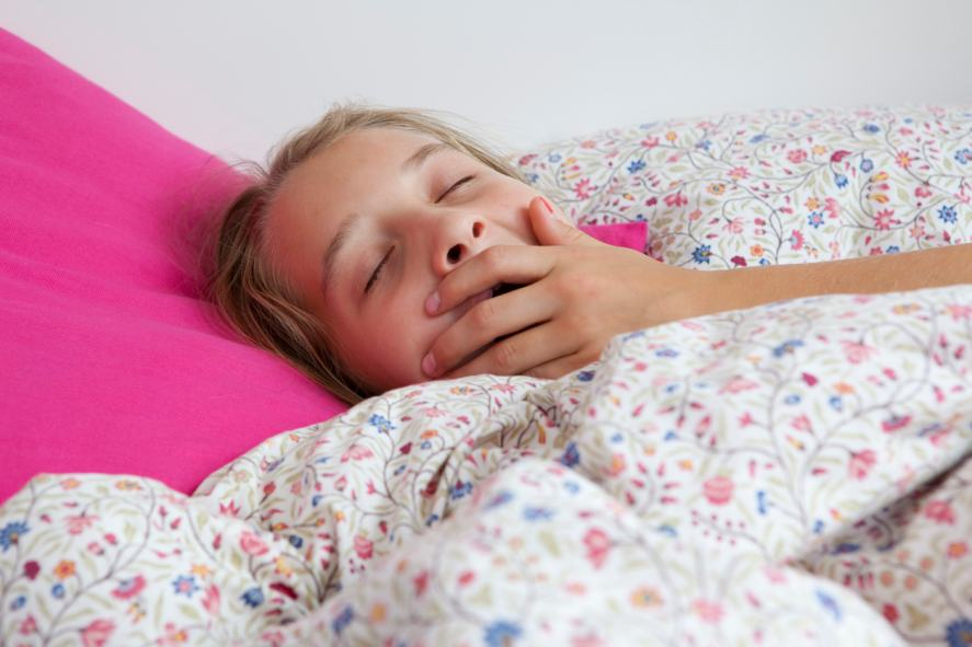 A close up of a child yawning in bed