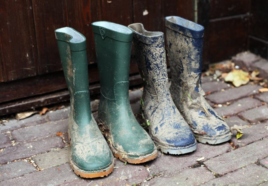 Two pairs of muddy boots outside a house