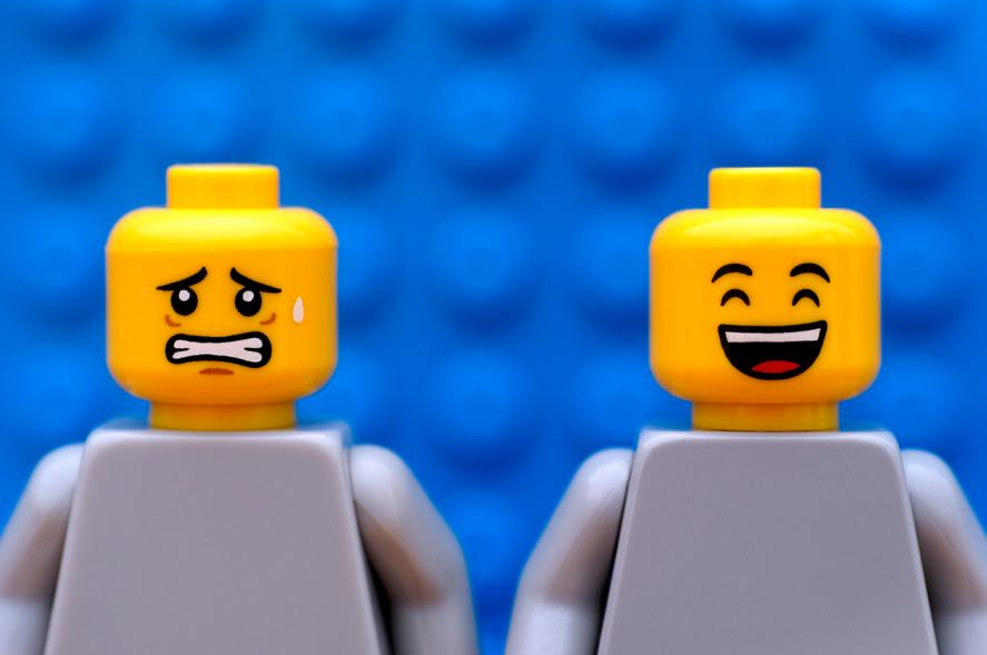 Two LEGO figures, one laughing, one looks uneasy
