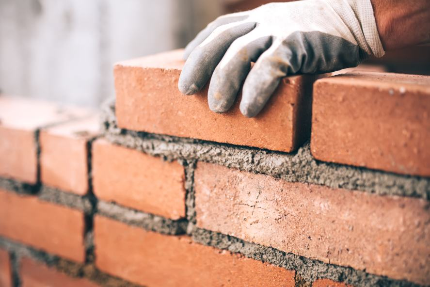 A person laying bricks with mortar