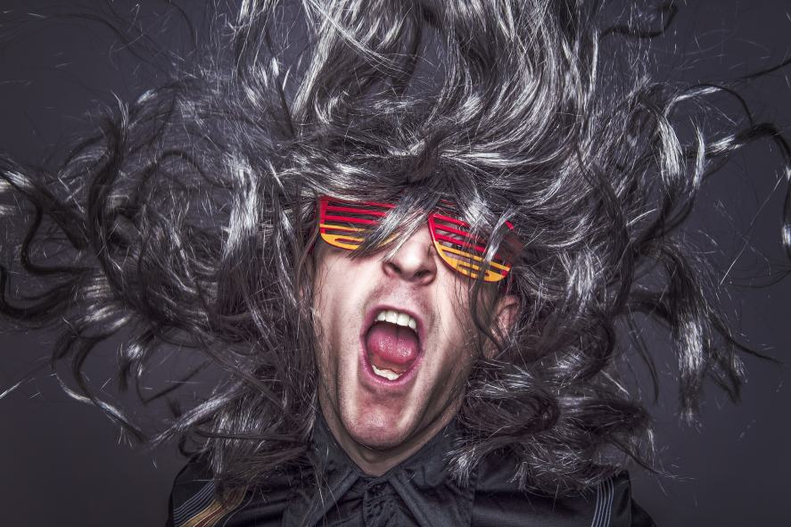 A man in sunglasses with a massive hairstyle