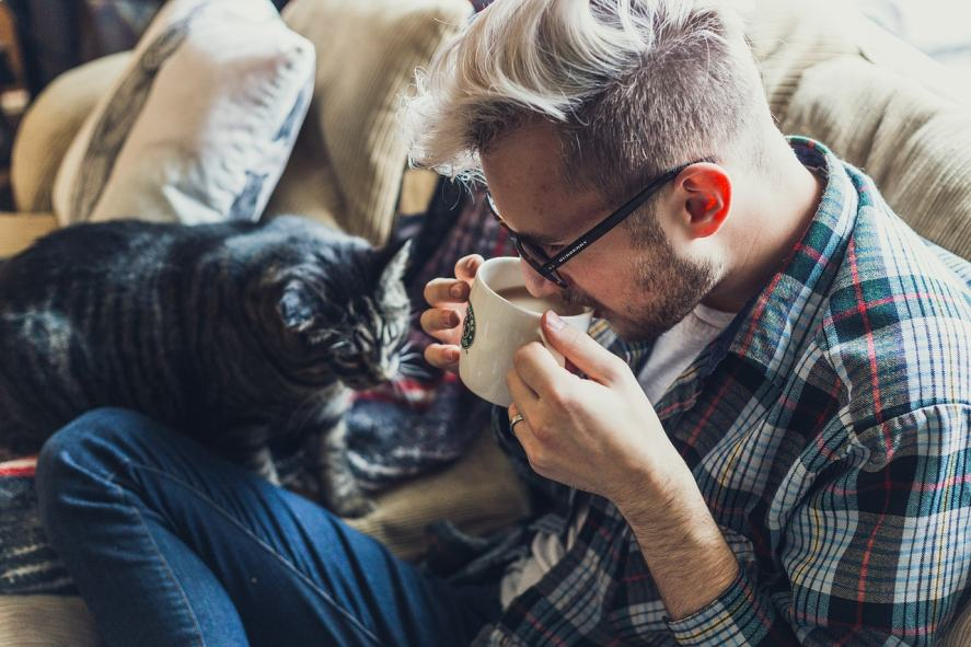 A man shielding his coffee from a thirsty pet