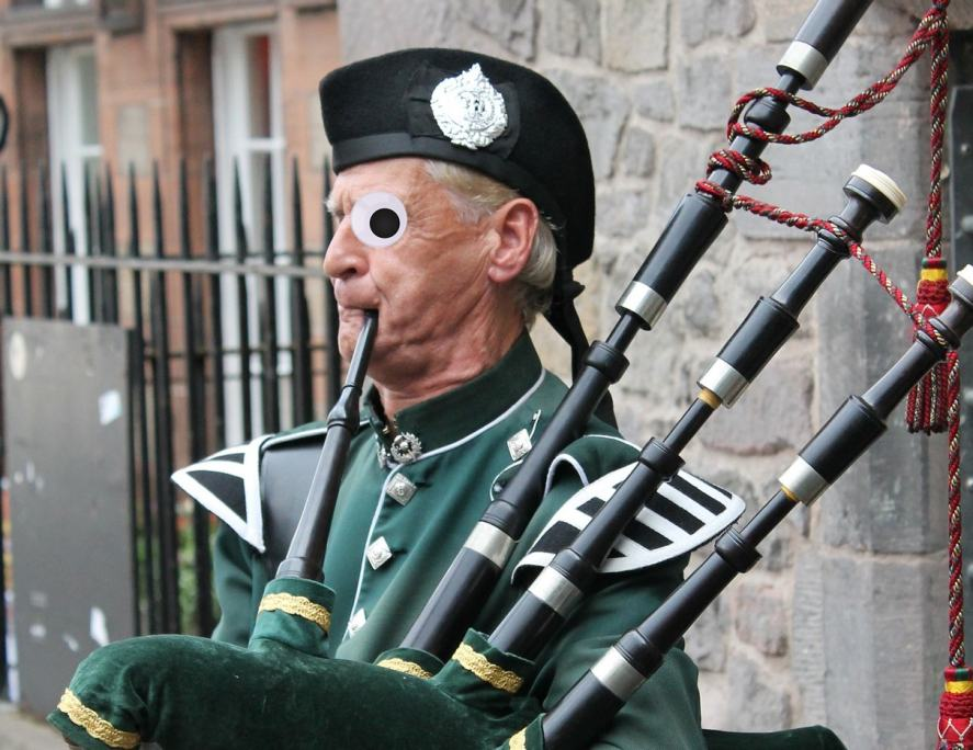 An elderly man blasting away on the bagpipes