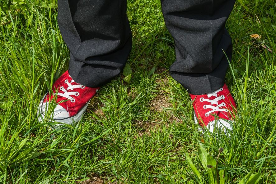A pair of black baggy trousers and a pair of red trainers
