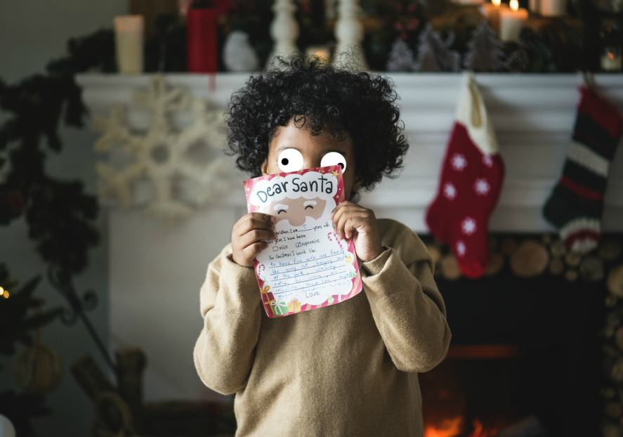 A child holds a letter to Santa
