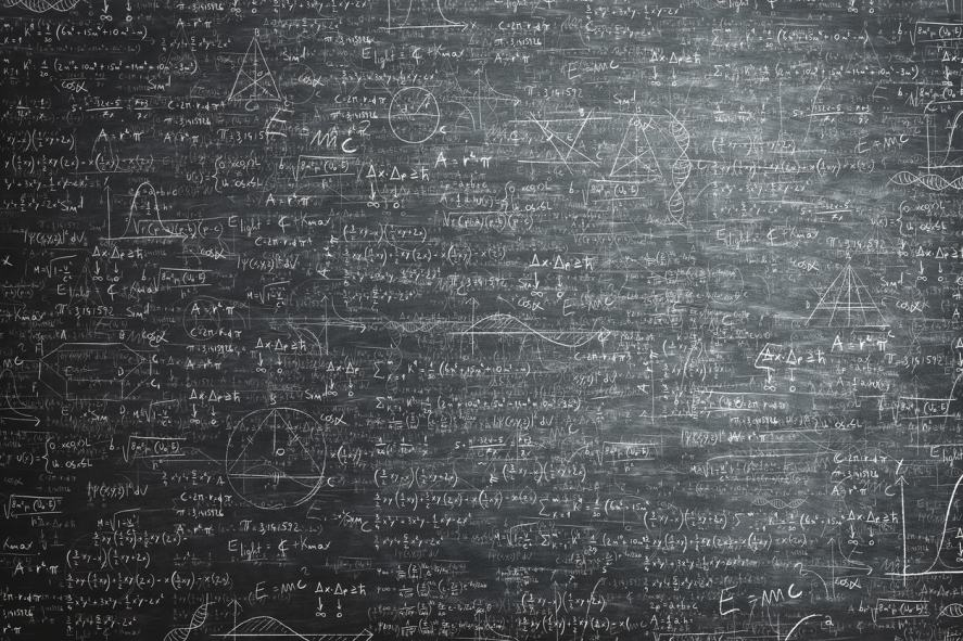 A chalk board covered in loads of maths