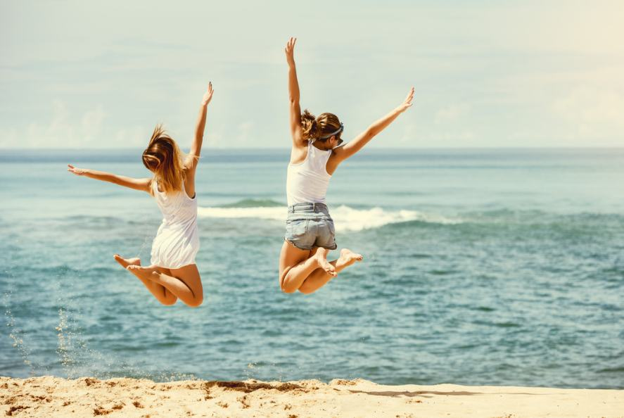 Two friends practice jumping on the beach