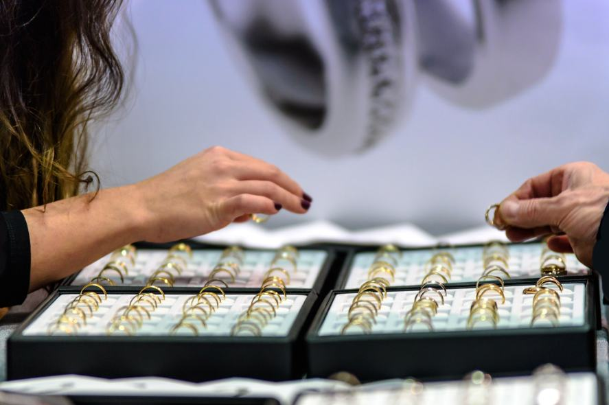 Two people browse gold rings in a jewellery shop