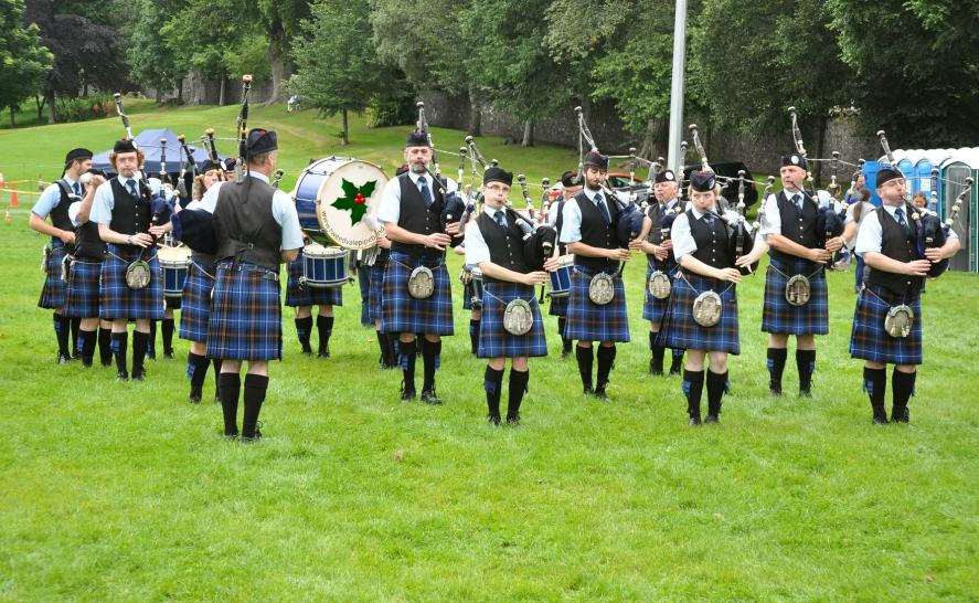 A group of bagpipe players performing in a field