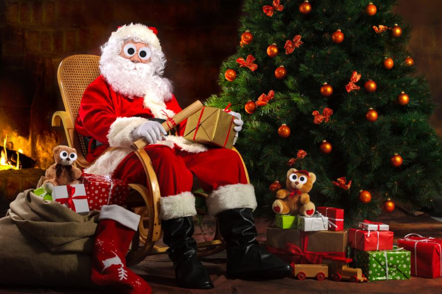 Santa Claus sitting on a rocking chair surrounded by presents