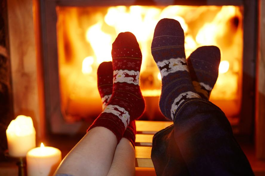 Two pairs of feet getting toasty by the fire