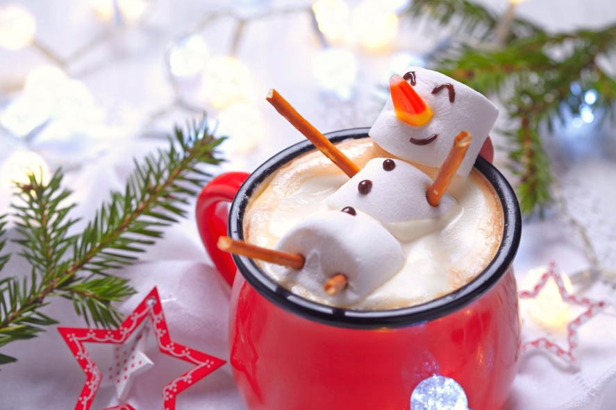 A marshmallow person relaxes in a mug of hot chocolate
