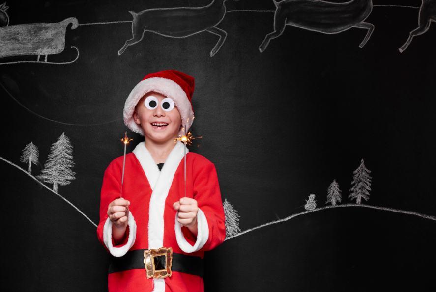 Child dressed up as santa claus enjoying a sparkler