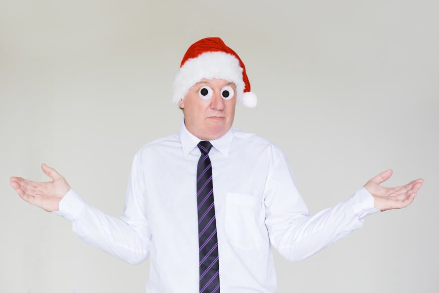 A shrugging man wearing a Santa hat and tie