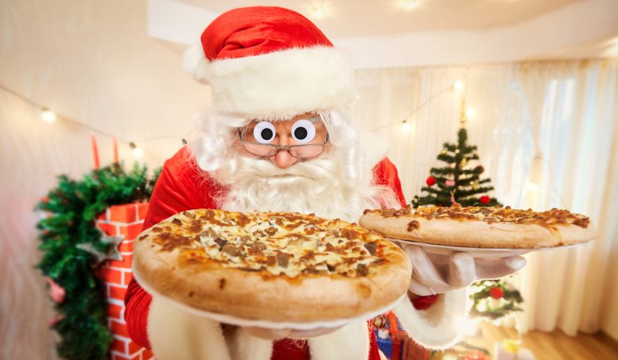 Santa holding two very large pizzas