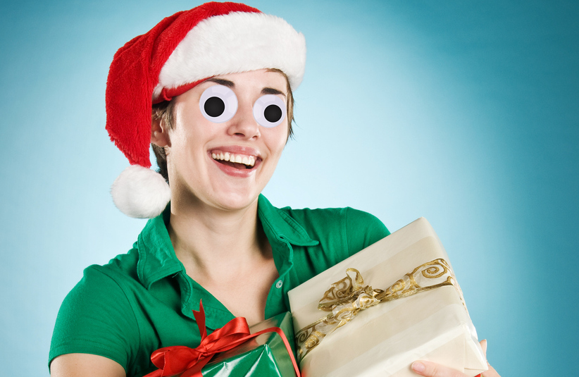 A woman in a Santa hat, holding a parcel