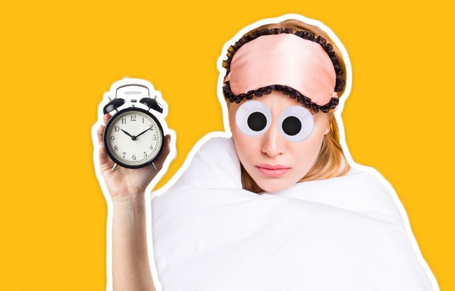 A sleepy woman holds an alarm clock
