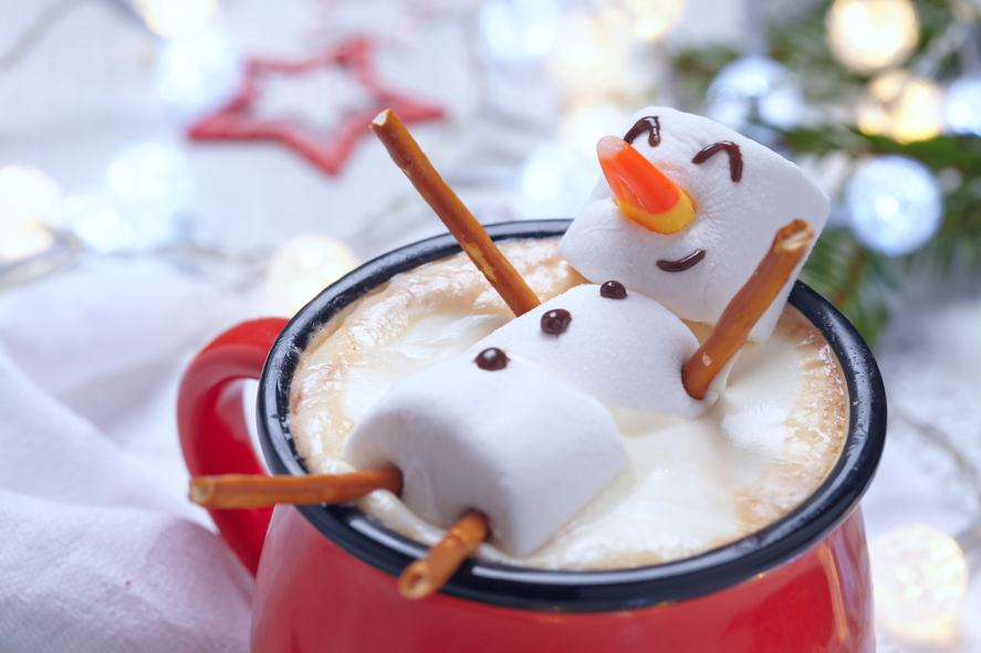 A marshmallow person relaxing in a mug of hot chocolate