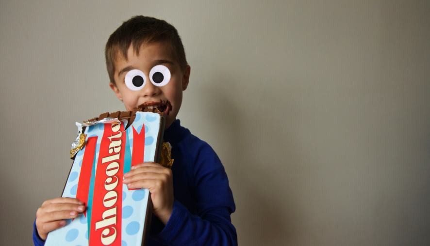 A child eating a massive bar of chocolate