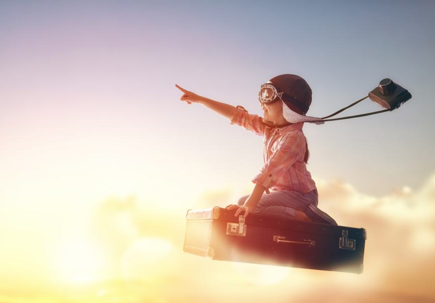 A child seating on a suitcase and flying through the clouds
