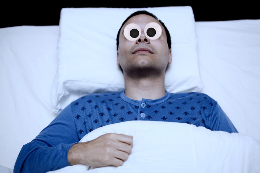 A person lying in bed wide awake
