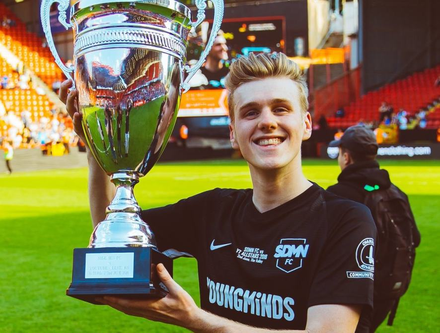 Lachlan holds up a football trophy
