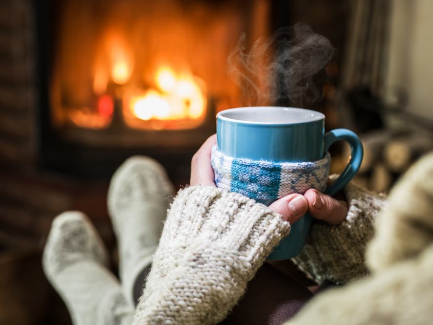 Someone relaxing with a hot drink in front of a roaring fire