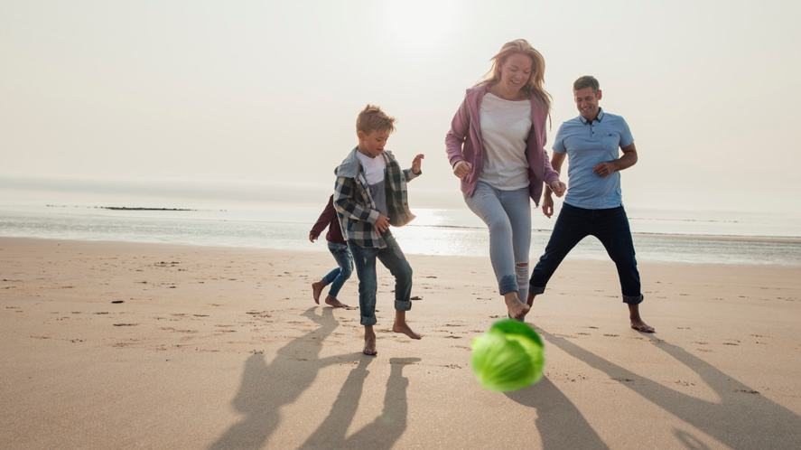 A family kicking a cabbage around on the beach