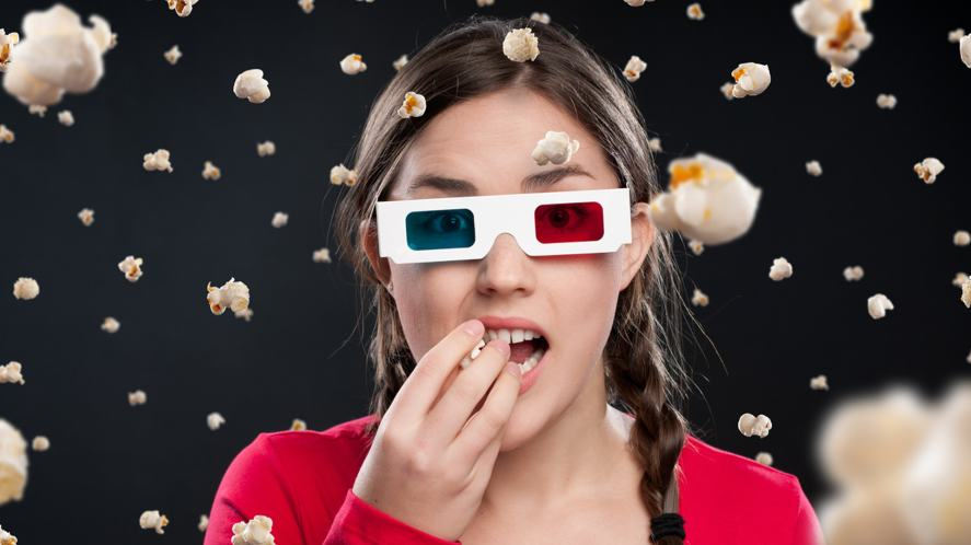 A person eating popcorn while wearing old-fashioned 3D glasses