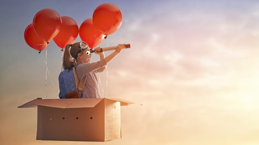 A girl flying around in a box suspended by red balloons