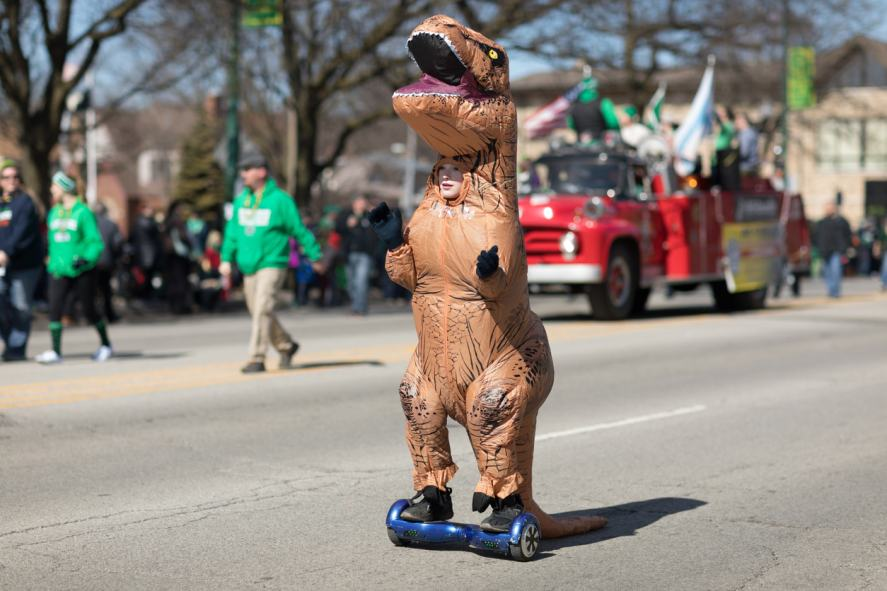A person dressed as a dinosaur on a hoverboard