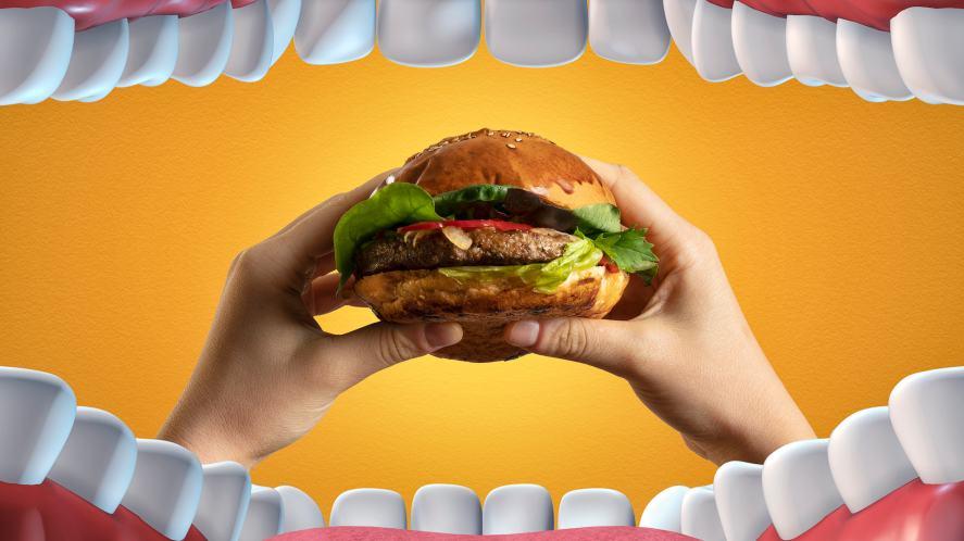 A big mouth prepares to take a bite of a sandwich