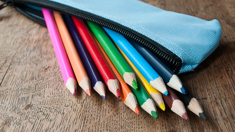 A pack of multicolored pencils lying on a wooden table