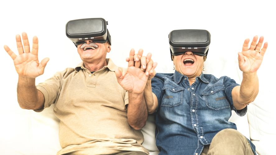 An elderly couple having fun together with virtual reality headset