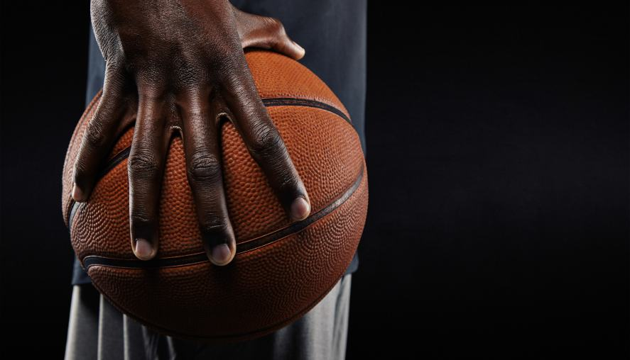 A man clutching a basketball with one band