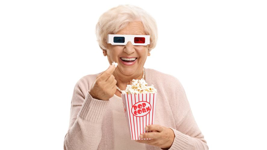A grandma eating popcorn in 3D glasses