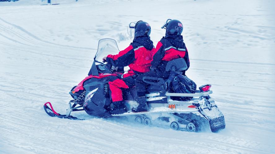 Couple riding snowmobile on frozen lake in winter